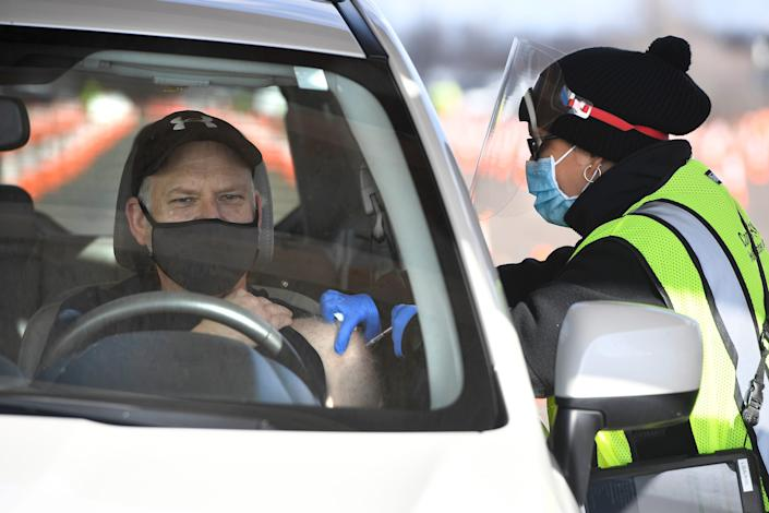 John Cormier receives a shot from LPN Lizmary Reyes, right, on the opening day of Connecticut's largest COVID-19 Vaccination Drive-Through Clinic on Monday in East Hartford.