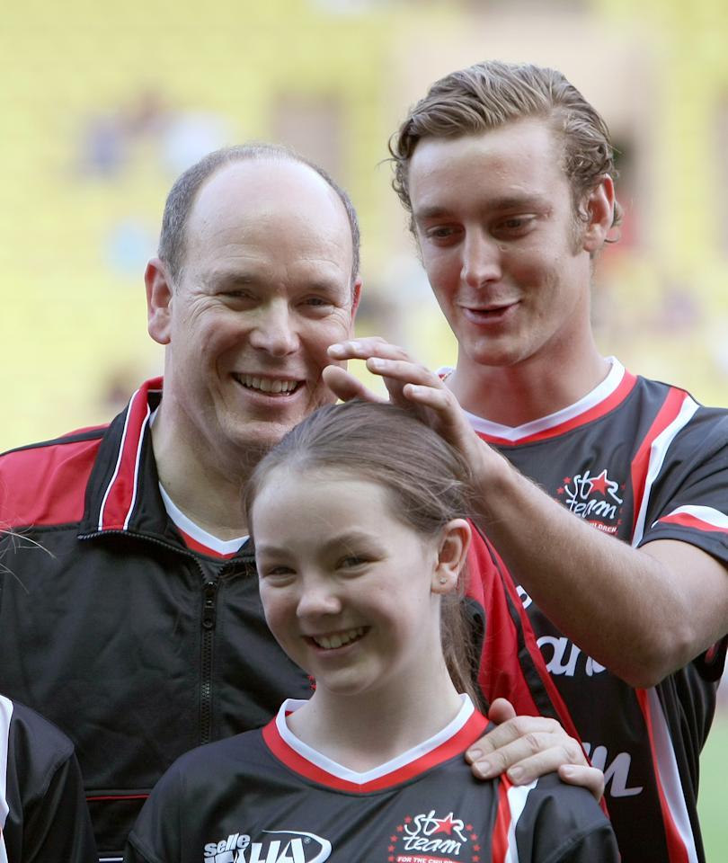 CORRECTS NAME OF BENEFIT - SAS Prince Albert II de Monaco, left, Pierre Casiraghi of Star Team for Children , right, son of Princess Caroline of Hanover, and Alexandra of Hanover daughter of Princess Caroline of Hanover, at the beginning of their charity soccer match against a Formula One Drivers team, in Monaco stadium,Tuesday, May 24, 2011. The match was set up for the benefit of the Association Centenary of the Cathedral of Monaco, to rebuild the church of Port au Prince, Haiti.