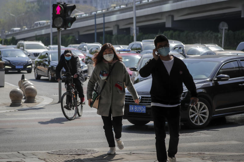 Pictured is a street crossing in Beijing with two pedestrians wearing masks as is a passing cyclist