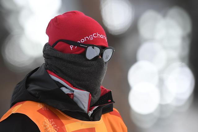 <p>An Olympic volunteer protects himself from the cold before the men's 15km + 15km cross-country skiathlon at the Alpensia cross country ski centre during the Pyeongchang 2018 Winter Olympic Games on February 11, 2018 in Pyeongchang. / AFP PHOTO / Christof STACHE </p>