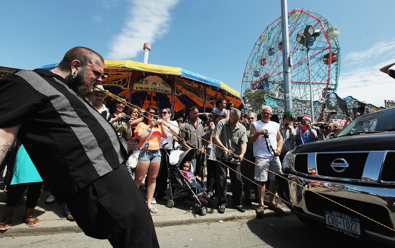 NEW YORK, NY - MAY 20:  A participant pulls trucks using his teeth during the Olde Time Coney Island Strongman Spectacular on May 20, 2012 in New York City. The old fashioned event featured participants who displayed feats of strength including bending wrenches, towing automobiles and lifting fire hydrants. (Photo by Mario Tama/Getty Images)