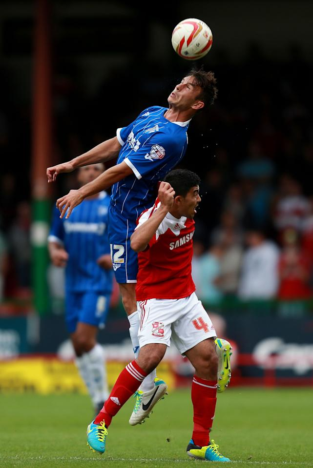 Gillingham's Steven Gregory wins a header from Swindon's Massimo Luongo during the Sky Bet Football League One match at the County Ground, Swindon.