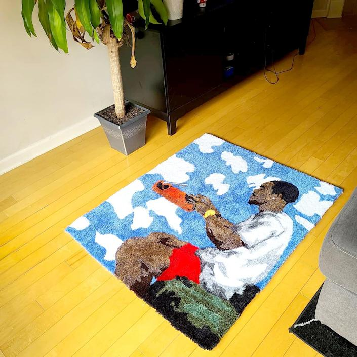 A rug depicts musician Frank Ocean seated and typing on a floating typewriter.