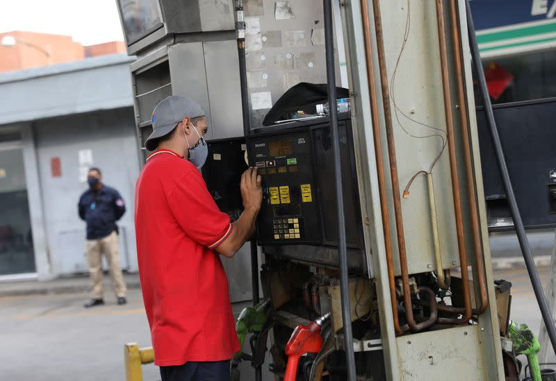A worker fixes a fuel dispenser machine at a gas station Caracas