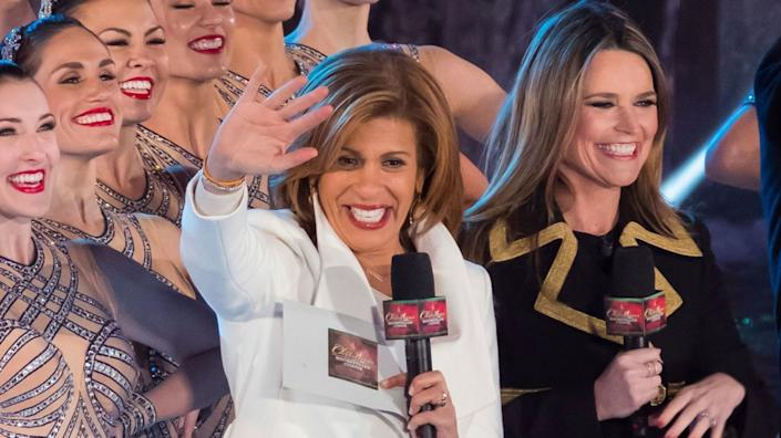 Hoda Kotb and Savannah Guthrie, holding microphones, stand alongside the Rockettes.