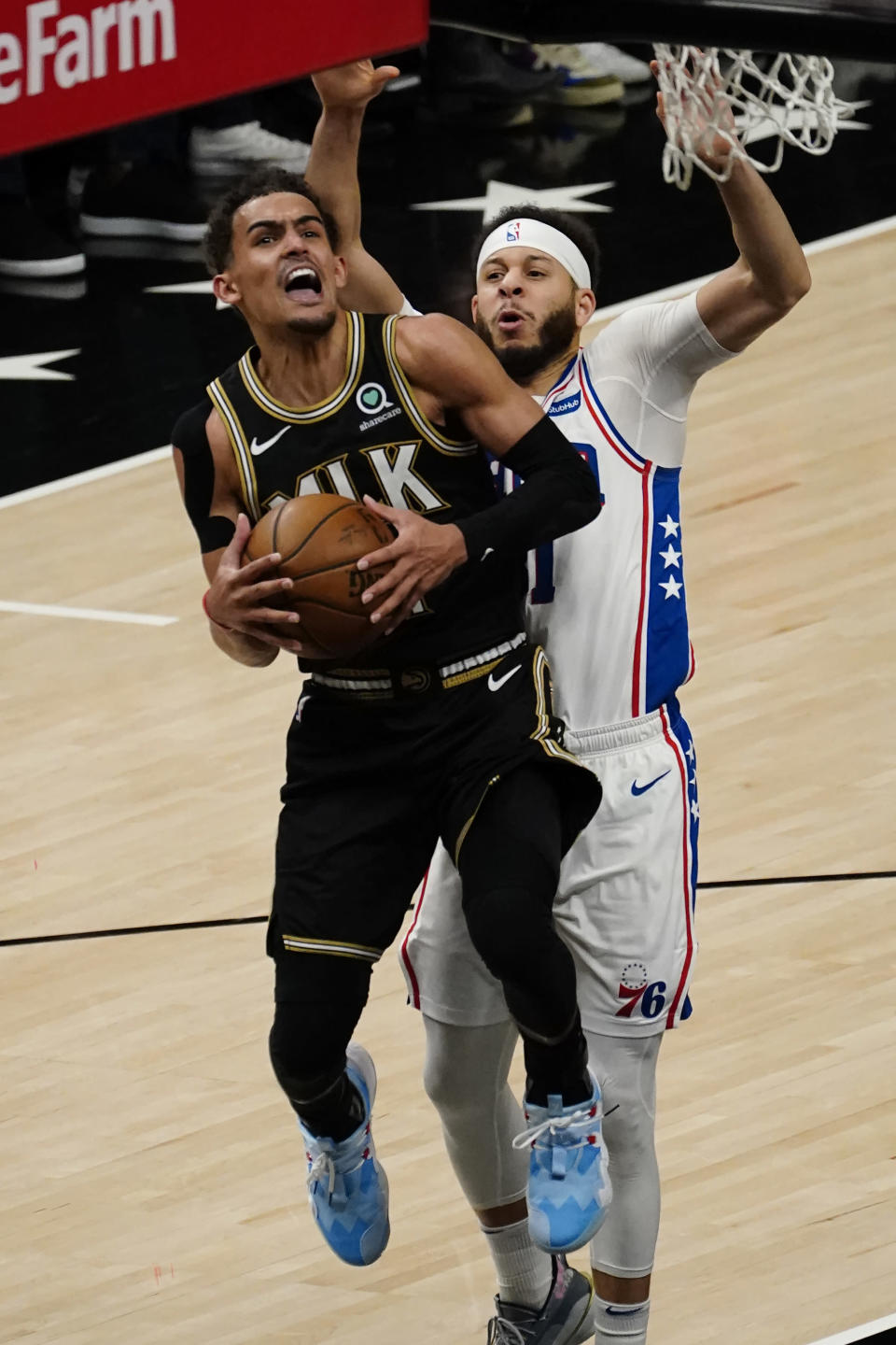 Atlanta Hawks guard Trae Young (11) goes up for a basket as Philadelphia 76ers guard Seth Curry (31) defends during the second half of Game 6 of an NBA basketball Eastern Conference semifinal series Friday, June 18, 2021, in Atlanta. (AP Photo/John Bazemore)