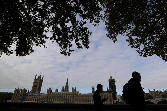 """People walk opposite Britain's Parliament in London, Friday, Oct. 16, 2020. Britain's foreign minister says there are only narrow differences remaining in trade talks between the U.K. and the European Union. But Dominic Raab insists the bloc must show more """"flexibility"""" if it wants to make a deal. (AP Photo/Kirsty Wigglesworth)"""