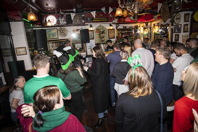 People celebrate St Patrick's Day at a Bristol Pub, a day after the government advised people to avoid social venues. (SWNS)