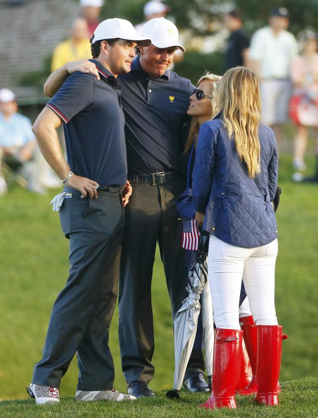 U.S. teammates Phil Mickelson (C) and Keegan Bradley (L) talk with Phil's wife Amy and Bradley's girlfriend after losing their first round match to the international team of Louis Oosthuizen and Charl Schwartzel of South Africa during the opening Four-ball matches for the 2013 Presidents Cup golf tournament at Muirfield Village Golf Club in Dublin, Ohio October 3, 2013. REUTERS/Jeff Haynes (UNITED STATES - Tags: SPORT GOLF)