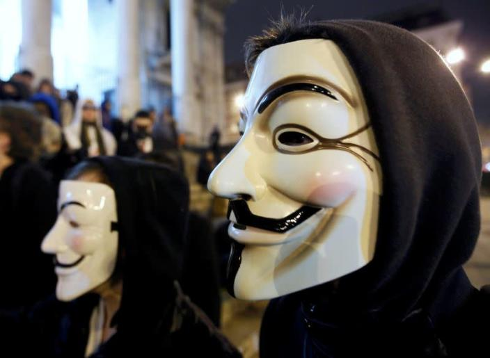 """FILE PHOTO: A protester wearing a Guy Fawkes mask, symbolic of the hacktivist group """"Anonymous"""", takes part in a protest in central Brussels"""