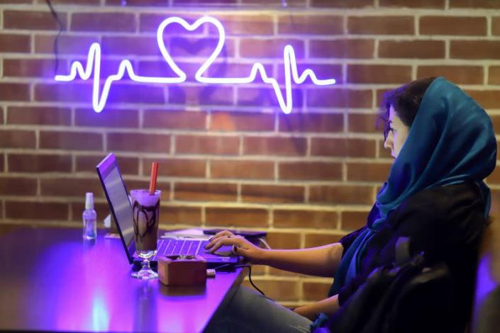 """An Iranian woman sits in a cafe after the launching of the """"Hamdam"""" dating app, in Tehran"""