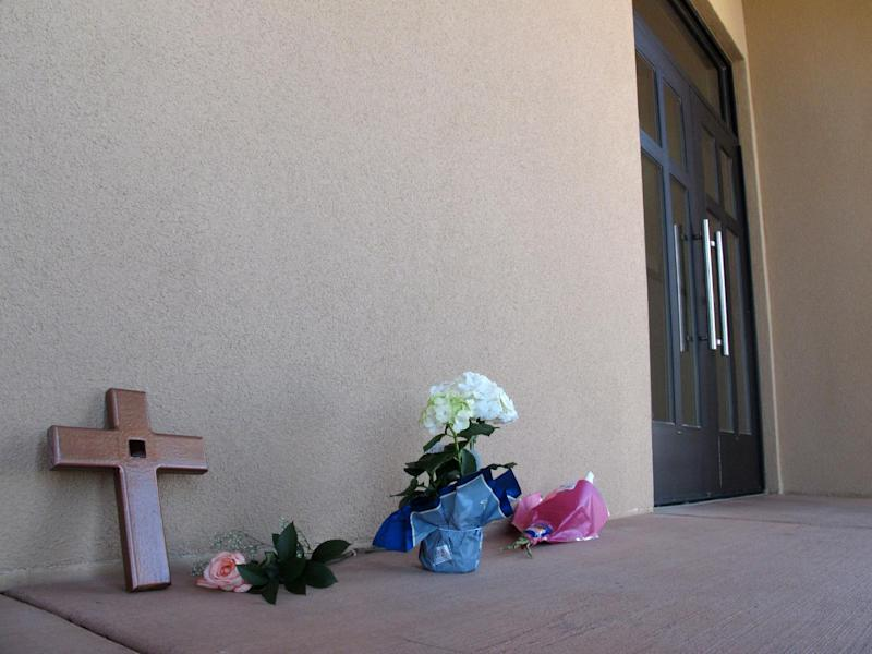A cross and flowers are left outside Monday, April 29, 2013 by a parishioner at the St. Jude Thaddeus Catholic Church in Albuquerque a day after a man stabbed several churchgoers Sunday as Mass was ending. Police say four parishioners were injured, including church choir director Adam Alvarez, but none have life-threatening injuries. Lawrence Capener, 24, is charged with three counts of aggravated battery and is being held on $75,000 bail. (AP Photo/Russell Contreras)