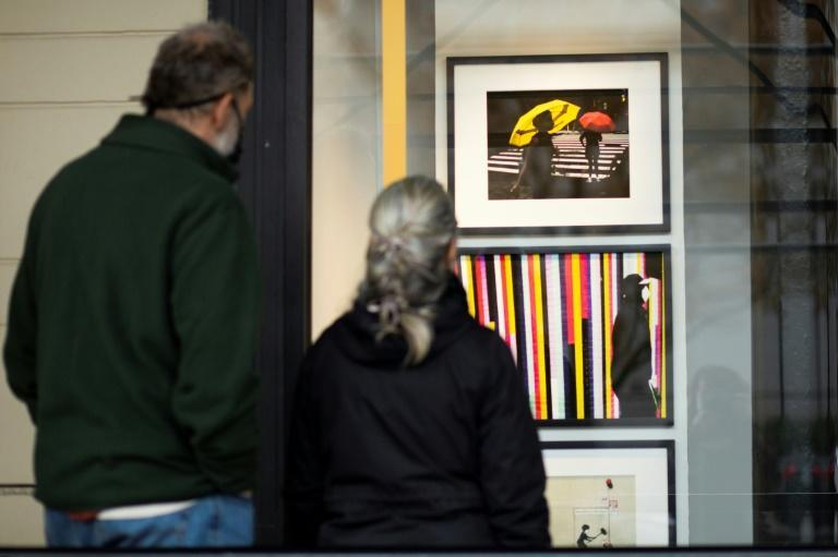 Art, including by artist Kevin Kinner seen here on November 28, 2020, is being displayed in unused retail spaces in the Art on the Ave exhibition in New York