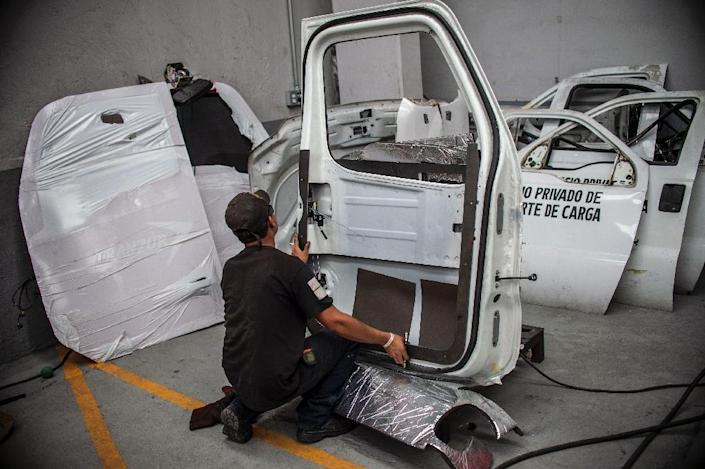Armored truck companies in mexico are coating tractor trailers in steel and putting bullet-proof glass in the windows to combat crime - it costs around 550,000 pesos ($27,000) to equip a semi-truck to withstand AK-47 fire (AFP Photo/Pedro PARDO)