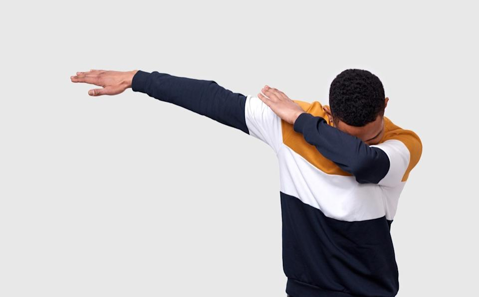 a man dabbing in front of a white wall