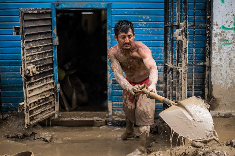 Residents of a populous district of Lima remove mud, debris and water left by a flash flood from their homes, on March 19, 2017 (AFP Photo/Ernesto BENAVIDES)