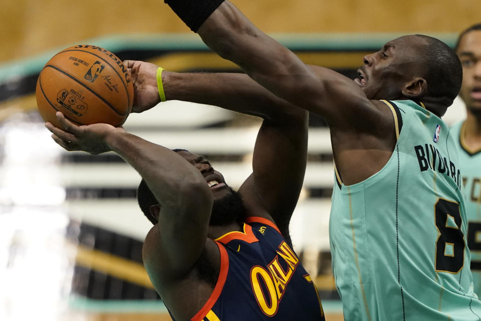 Charlotte Hornets center Bismack Biyombo, right, guards Golden State Warriors' Eric Paschall during the first half of an NBA basketball game on Saturday, Feb. 20, 2021, in Charlotte, N.C. (AP Photo/Chris Carlson)
