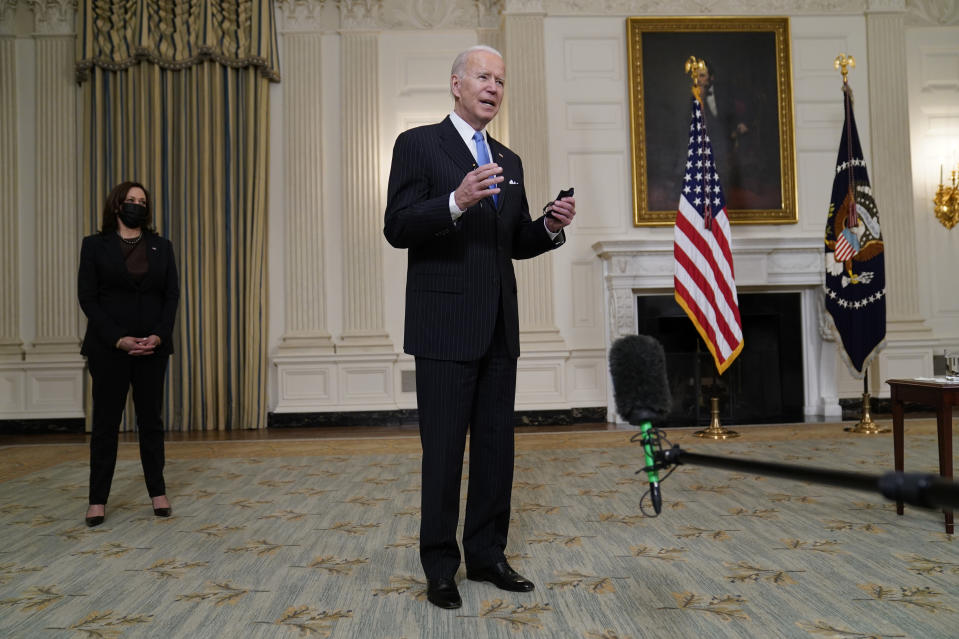 President Joe Biden holds a face mask after speaking about efforts to combat COVID-19, in the State Dining Room of the White House, Tuesday, March 2, 2021, in Washington. Vice President Kamala Harris is at left. (AP Photo/Evan Vucci)
