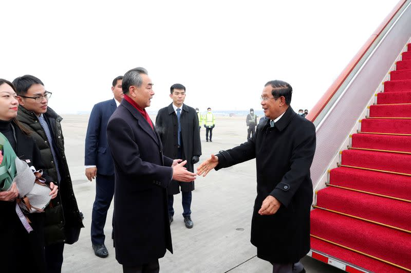 FILE PHOTO: Chinese State Councilor and Foreign Minister Wang Yi welcomes Cambodian Prime Minister Hun Sen as he arrives at the Beijing Capital International Airport