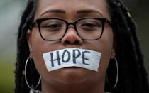 A woman wears a message on her mask as she holds a silent prayer for victims of the 1921 Tulsa Massacre on May 31, 2021
