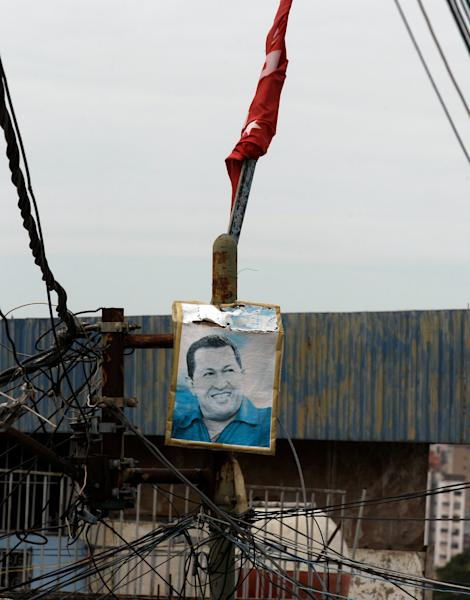 An image of Venezuela's President Hugo Chavez hangs from an electric pole at the neighborhood of Petare in Caracas, Venezuela, Monday, Dec. 17, 2012. Smarting after a bruising loss in state elections, Venezuela's opposition will now be forced to reassess its strategy and rebuild quickly to prepare for presidential elections that many expect could be called to replace Chavez. (AP Photo/Fernando Llano)