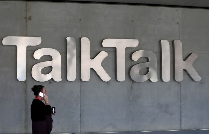 FILE PHOTO: A woman speaks on her phone as she passes a branded logo outside the Talktalk headquarters in London