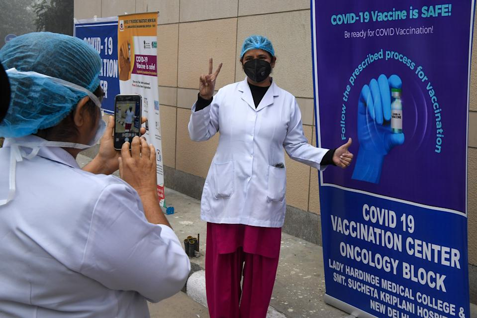 A healthcare worker poses for a photo beside a poster about the Covid-19 coronavirus vaccine at the Kalawati hospital in New Delhi on January 16, 2021. (Photo by Prakash SINGH / AFP) (Photo by PRAKASH SINGH/AFP via Getty Images)