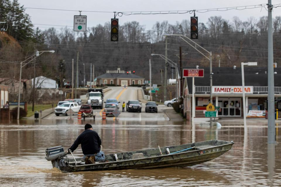 Justin Wade drives a boat down Main Street after high water and flooding filled downtown Beattyville after heavy rains led Kentucky River waters overflowing Sunday evening. March 1, 2021