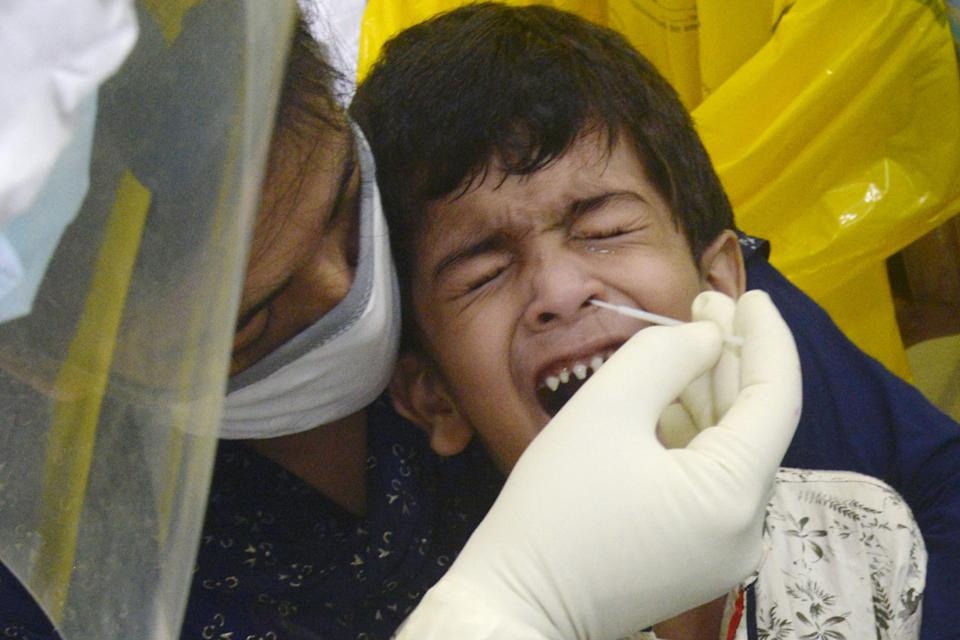 A health worker collects a swab sample from a child for antigen rapid test for Covid-19 in Kolkata on August 8, 2020. (Photo: Pacific Press via Getty Images)