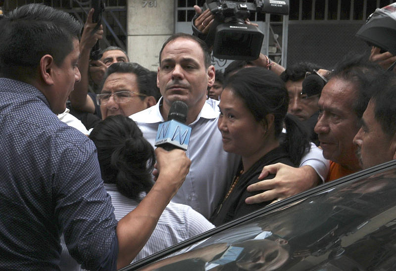 Keiko Fujimori, the daughter of Peru's former President Alberto Fujimori and opposition leader with her husband Mark Vito Villanela, enters to the courtroom in handcuffs in Lima, Peru, Tuesday, Jan. 28, 2020. In a court session a judge decided she must return to preventive detention pending a corruption investigation. (AP Photo/Martin Mejia)