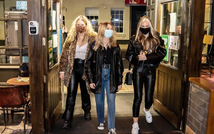 Left to right Rebecca Mitchell, Rosie Delaney and Isobel Logan enter the Showtime Bar at 00:02 in Huddersfield - Danny Lawson/PA
