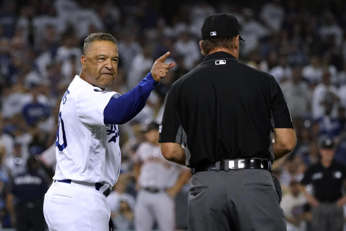 Los Angeles Dodgers manager Dave Roberts, left, argues with first base umpire Ed Hickox after San Francisco Giants' Darin Ruf walked with the bases loaded during the ninth inning of a baseball game Thursday, July 22, 2021, in Los Angeles. (AP Photo/Marcio Jose Sanchez)
