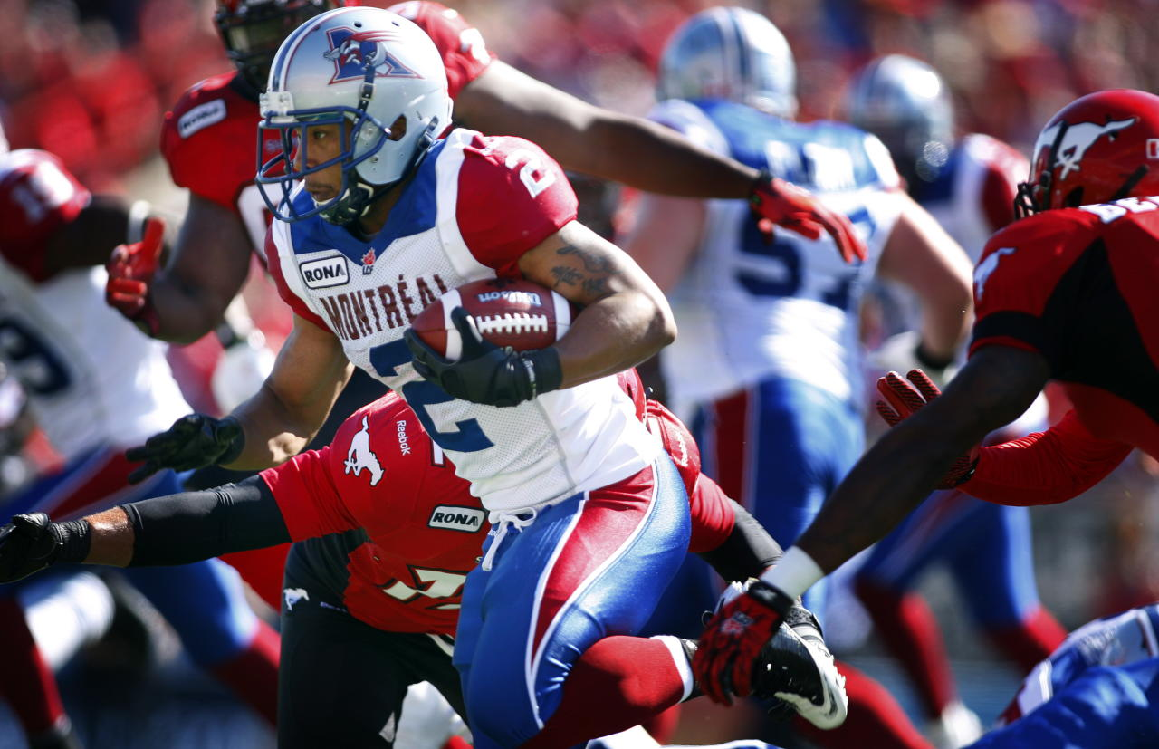 Montreal Alouettes' Brandon Whitaker, left, runs through Calgary Stampeders' defenders during first half CFL football action in Calgary, Alta., Sunday, July 1, 2012. THE CANADIAN PRESS/Jeff McIntosh