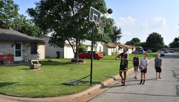 Malique Young, left, Ian Polvado, Kilar Hill and Lane Hill, right,  shoot baskets on a goal set up in Kari Hill's front yard. The city had cited her for encroachement.