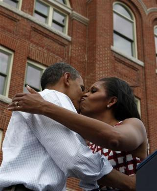 First lady Michelle Obama and Barack Obama kiss on stage before he speaks at a campaign event at the Alliant Energy Amphitheater in Dubuque, Iowa, August 15, 2012.