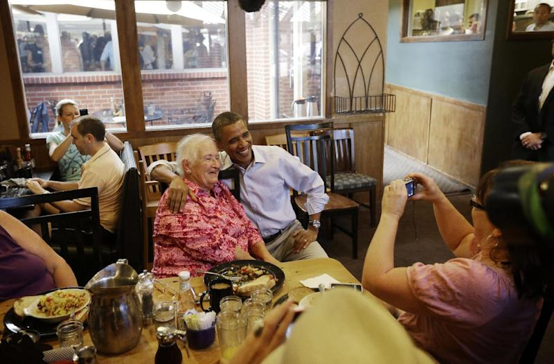 President Barack Obama, center, poses for a photograph with Barbara McClusky, 78, as he greets patrons during an unscheduled stop at the Buff Restaurant, Sunday, Sept. 2, 2012, in Boulder, Colo. (AP Photo/Pablo Martinez Monsivais)
