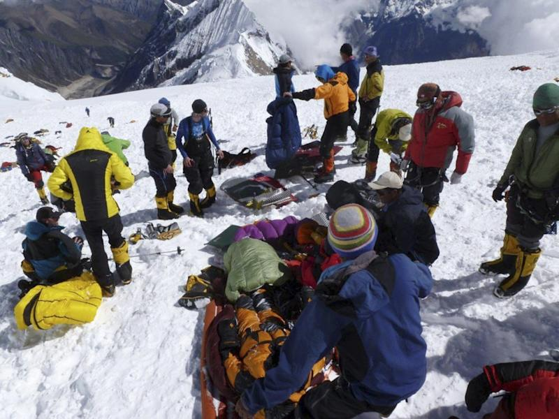 In this picture taken Sunday, Sept. 23, 2012 and released by Alpine Ascents International, rescuers and climbers prepare survivors for evacuation from the debris field of an avalanche on Mount Manaslu in northern Nepal. Rescue helicopters flew over the high slopes of the northern Nepal peak again Monday to search for climbers lost in an avalanche that killed at least nine mountaineers and injured others. Many of the climbers were French, German and Italian. (AP Photo/Garrett Madison, Alpine Ascents International)