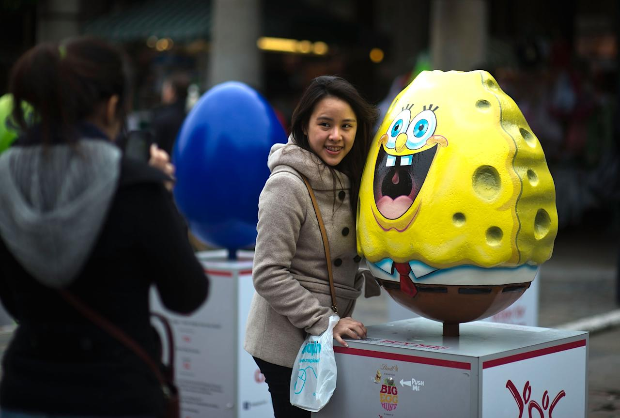 LONDON, ENGLAND - MARCH 22:  A visitor poses for a photograph with an egg entitled ' SpongeBob SquarePants' by Nicktoons, one of the giant fibreglass easter eggs on display in Covent Garden before the Big Egg Hunt on March 22, 2013 in London, England. Each egg is two and a half feet tall and designed by a leading artist.  (Photo by Bethany Clarke/Getty Images)