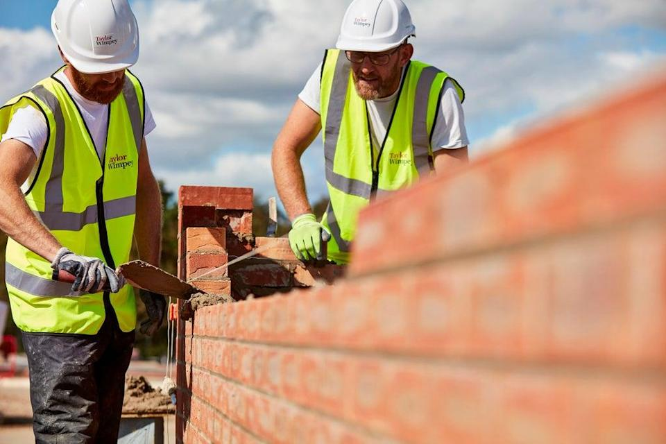 Workers laying bricks at a construction site (Taylor Wimpey/PA) (PA Media)