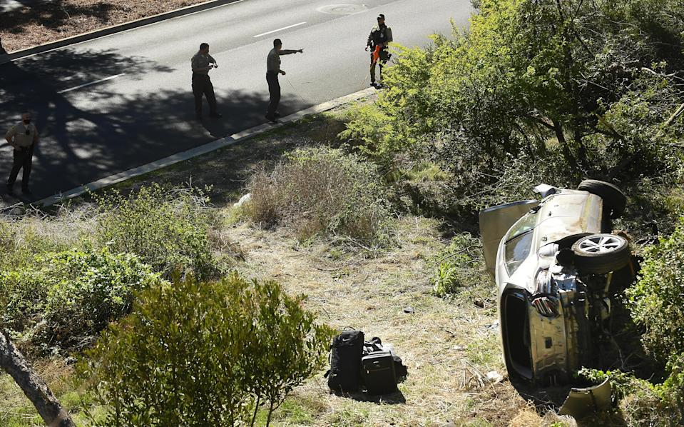 Sheriff deputies investigate the scene where Tiger Woods crashed his SUV on February 23, 2021. / Credit: Wally Skalij/Los Angeles Times via Getty