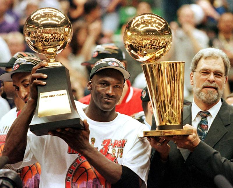 (FILES) In this 14 June 1998 file photo, Michael Jordan (L) holds the NBA Finals Most Valuable Player trophy and former Chicago Bulls head coach Phil Jackson holds the NBA champions Larry O'Brian trophy 14 June after winning game six of the NBA Finals with the Utah Jazz at the Delta Center in Salt Lake City, UT. The Bulls won the game 87-86 to take their sixth NBA championship. Jackson left the Bulls following the 1998 season and 12 January reports indicate that Jordan plans to announce his retirement at a 13 January news conference in Chicago. AFP PHOTO/FILES/Jeff HAYNES (Photo by JEFF HAYNES / AFP) (Photo by JEFF HAYNES/AFP via Getty Images)