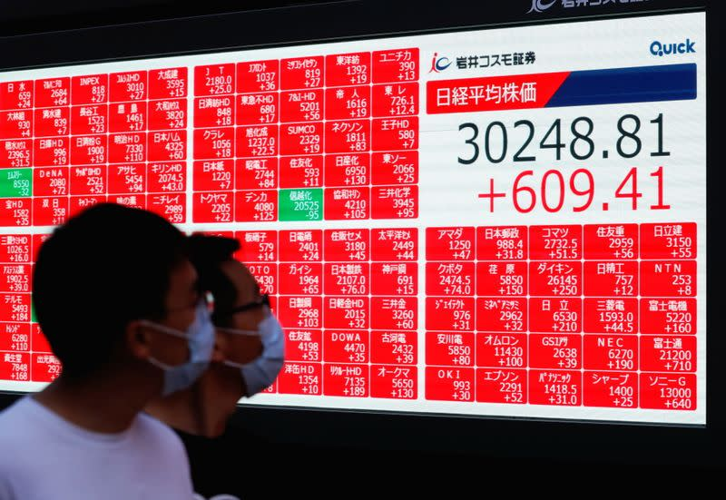 Men wearing protective face masks amid the coronavirus disease (COVID-19) outbreak look at an electronic board displaying Japan's Nikkei Index outside a brokerage in Tokyo
