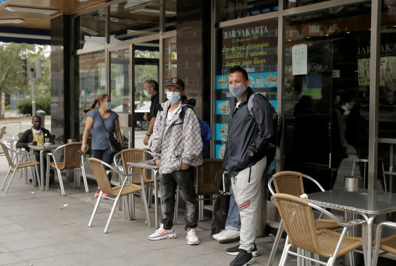 People wearing protective face masks stand at Usera neighbourhood in Madrid