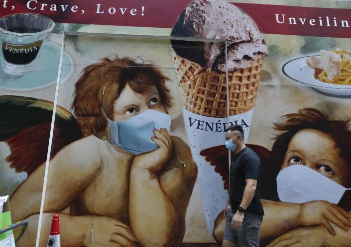 A man wearing a face mask to prevent the spread of the coronavirus walks past a huge poster on a street in Hong Kong, Wednesday, May 12, 2021. (AP Photo/Vincent Yu)