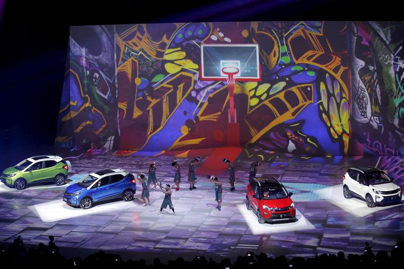 FILE PHOTO: Performers perform next to BYD's hybrid electric cars 'Yuan' on a stage at BYD Dreamcast conference in Beijing