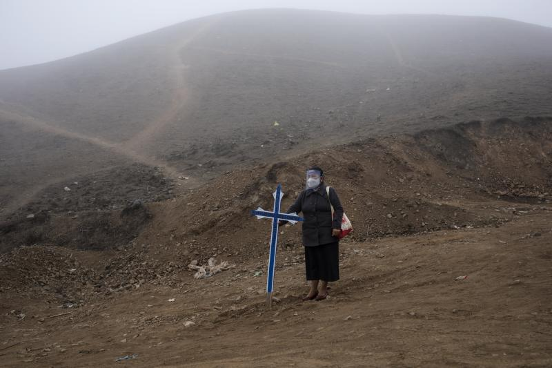 Noly Suarez holds a cross during the burial of her brother Flavio Juarez, 50, who died of COVID-19, at the Nueva Esperanza cemetery on the outskirts of Lima, Peru, Tuesday, May 26, 2020. (AP Photo/Rodrigo Abd)