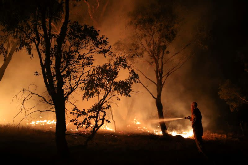 FILE PHOTO: A firefighter works to extinguish flames after a bushfire burnt through the area in Bredbo
