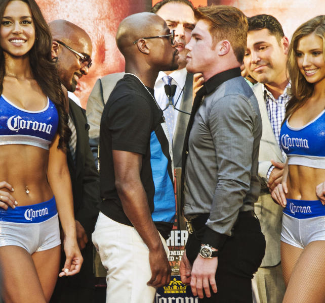 "Floyd Mayweather, center left, poses in a face-off with Saul ""Canelo"" Alvarez during a boxing news conference on Monday, June 24, 2013, at New York's Times Square. MayWeather and Alvarez kicked-off an 11-city promotional, making their fight in Las Vegas in September official. The undefeated fighters announced on Twitter last month that they would face each other at the MGM Grand on Sept. 14. (AP Photo/Bebeto Matthews)"