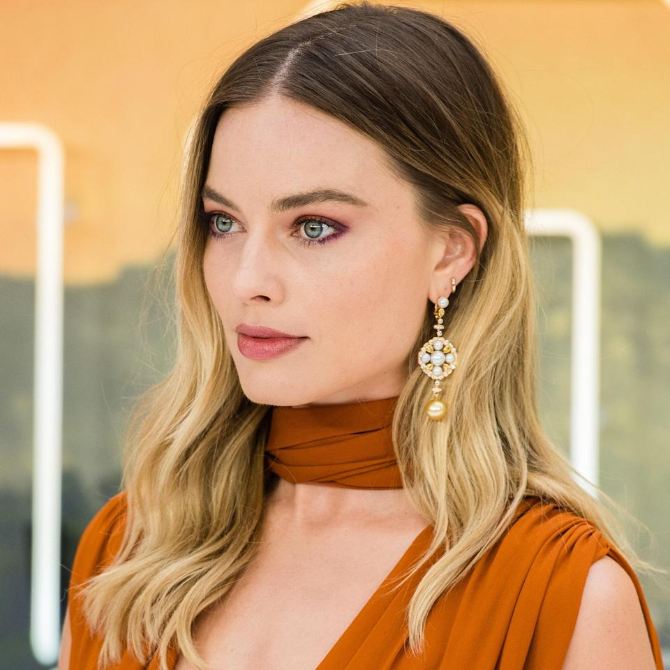"""This high-contrast ombré on Margot Robbie has a burst of brightness that's super low-maintenance — all the more reason to try it yourself. """"This summertime look works year-round and [enhances her eyes],"""" says colorist <a href=""""https://www.instagram.com/guy_tang/"""" rel=""""nofollow noopener"""" target=""""_blank"""" data-ylk=""""slk:Guy Tang"""" class=""""link rapid-noclick-resp"""">Guy Tang</a>. Tang also advises that a good <a href=""""https://www.allure.com/gallery/best-purple-shampoo-conditioner-blonde-hair?mbid=synd_yahoo_rss"""" rel=""""nofollow noopener"""" target=""""_blank"""" data-ylk=""""slk:purple shampoo"""" class=""""link rapid-noclick-resp"""">purple shampoo</a> like <a href=""""https://shop-links.co/1700636339656634663"""" rel=""""nofollow noopener"""" target=""""_blank"""" data-ylk=""""slk:this customizable one from Function of Beauty"""" class=""""link rapid-noclick-resp"""">this customizable one from Function of Beauty</a> can help maintain brightness on the mids and ends of a look like this."""