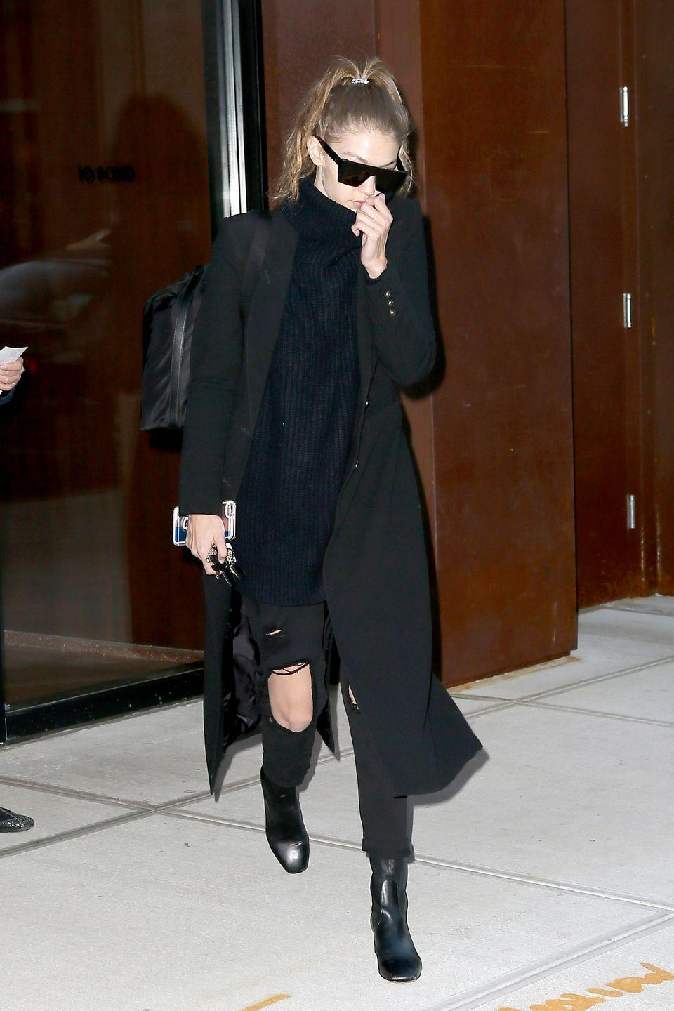 """<p>Heading to New York's JFK airport, Gigi wore a black turtleneck with distressed <a href=""""http://www.7forallmankind.com/josefina-with-open-holes-in-black-/d/13158C26506?CategoryId=3310"""" rel=""""nofollow noopener"""" target=""""_blank"""" data-ylk=""""slk:7 For All Mankind"""" class=""""link rapid-noclick-resp"""">7 For All Mankind</a> jeans, a black Smythe coat and Sandro ankle boots. </p>"""